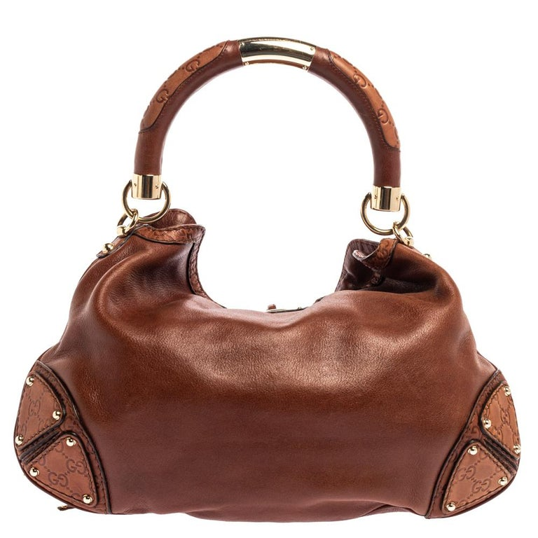 Crafted from leather, this Gucci number has a top with two bamboo-detailed tassels and a spacious fabric interior. It also features a sturdy top handle, armoured GG-printed corners, and gold-tone hardware. Flaunt this beauty wherever you go and