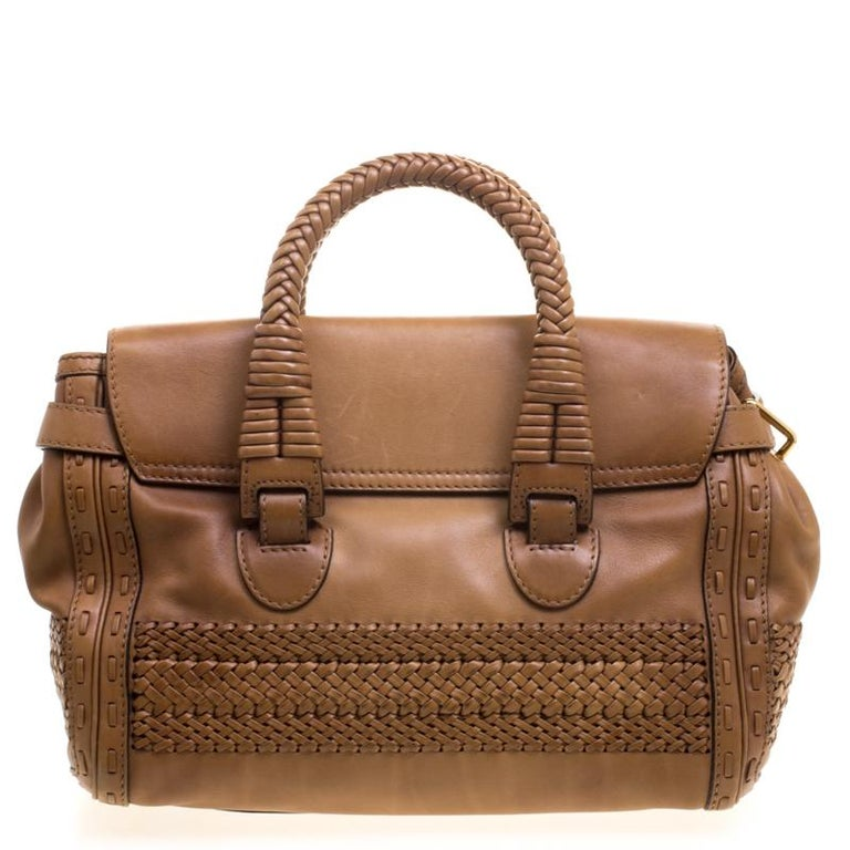 From the legendary house of Gucci, this bag is designed in a brown leather and detailed with tonal stitching. It comes with two top rolled handles and opens to a suede interior fitted with a zip wall pocket. Carry it in the crook of your arm to