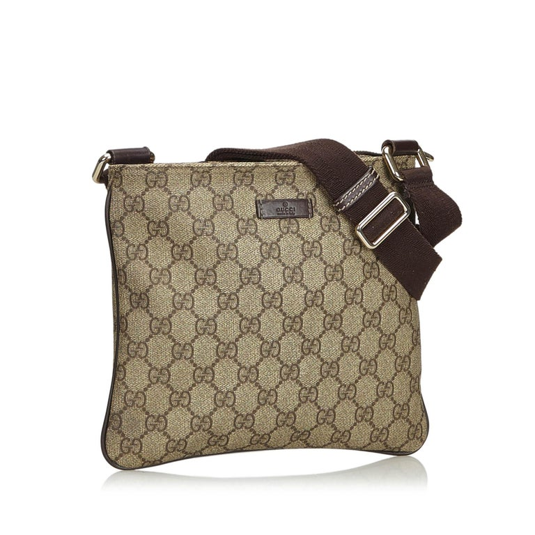 7725eba3b This crossbody bag features a coated canvas body, a flat strap, a top zip