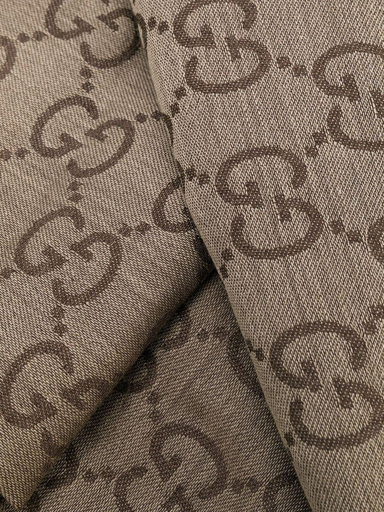 Crafted in Italy from an intricate blend of wool and silk in a neutral palette of brown and taupe, this monogram print scarf from Gucci features an all-over GG Jacquard print design and fringed edges.  Colour: Brown/ Taupe  Composition: 70% Wool,