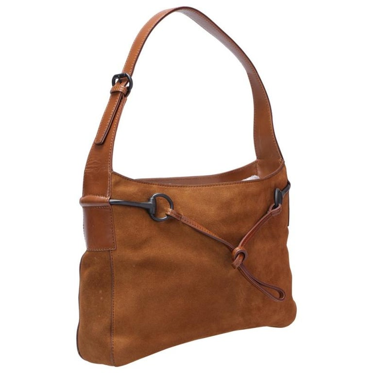 This Horsebit shoulder bag by Gucci is crafted from brown suede and leather. Fine fabric interior ensures to house your essentials safely. Equipped with an adjustable top handle, it has a brilliant finishing and design. Simple and chic is what this