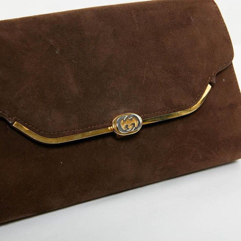 This GUCCI vintage bag is in brown suede. Closure by press button. The jewelry is in golden metal with the acronym