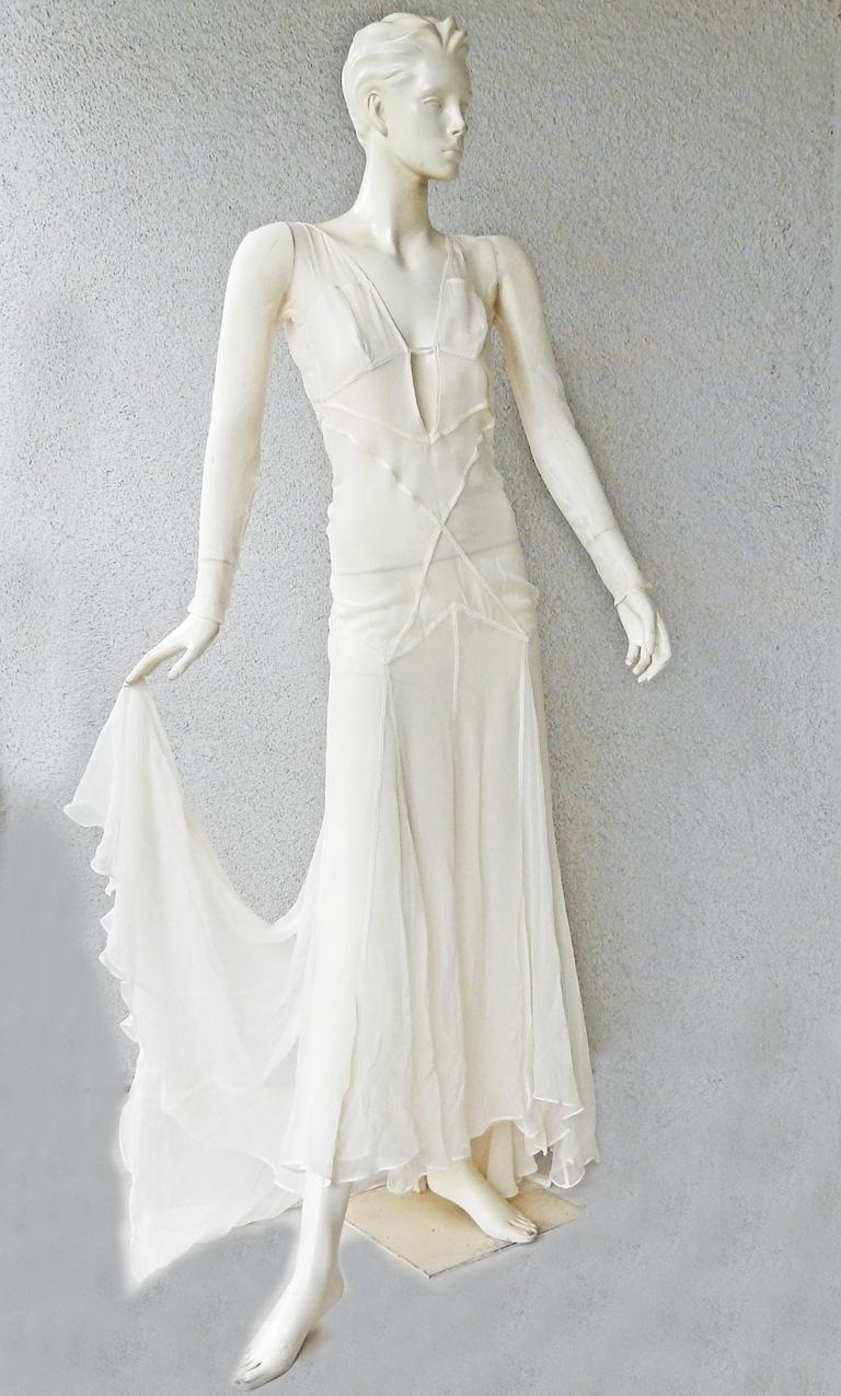A rare Gucci by Tom Ford 2002 evening dress fashioned in eggshell white outlined in eye catching seam illusion.   Dress boasts a tasteful plunging neckline extending into a full skirt with dramatic train.   Criss-cross design open back.  Side snap