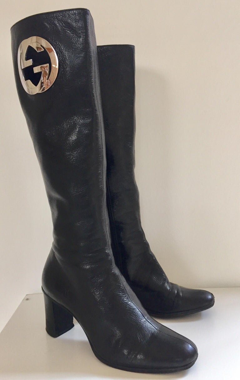 Tom Ford's Gucci pair of knee-high leather boots, circa 1999. In a sleek silhouette, these Gucci boots are crafted in black lamb supple leather, finished with a block heel, side zipper and a prominent monogram in silver tones on only one