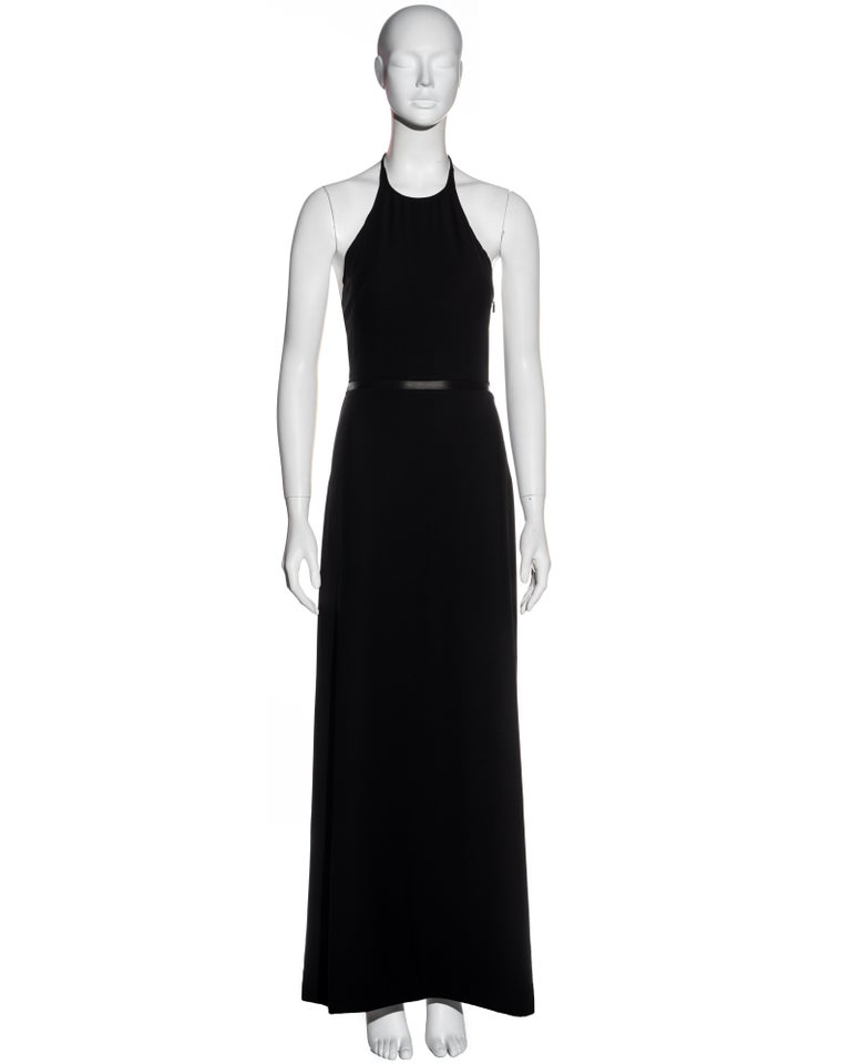 ▪ Gucci black wool halter neck maxi dress ▪ Designed by Tom Ford ▪ Black leather waistband  ▪ Fitted bodice ▪ A-line maxi skirt  ▪ Concealed zipper at side seam  ▪ Gold 'G' pendent detail ▪ New with tags ▪ IT 38 - FR 34 - UK 6 - US 2 ▪ Fall-Winter
