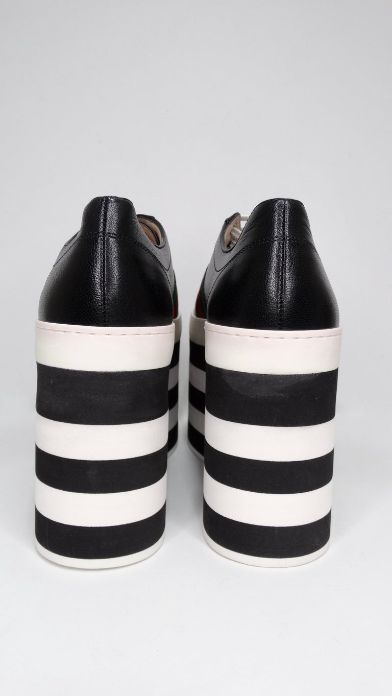 Make a statement with these funky sneakers! These shoes feature calf leather, rounded roes, and a black and white striped 4.5 inch platform with the iconic red and green Gucci colors accenting the shoe. Slight scuffing on platform as shown in