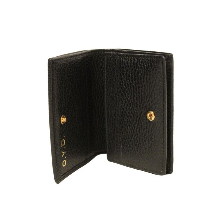 Gucci card case wallet with small GG in gold toned metal detail. Made in beautiful black textured leather with five card slots, bill compartment, interior zipper coin pocket and snap closure.  Made in Italy