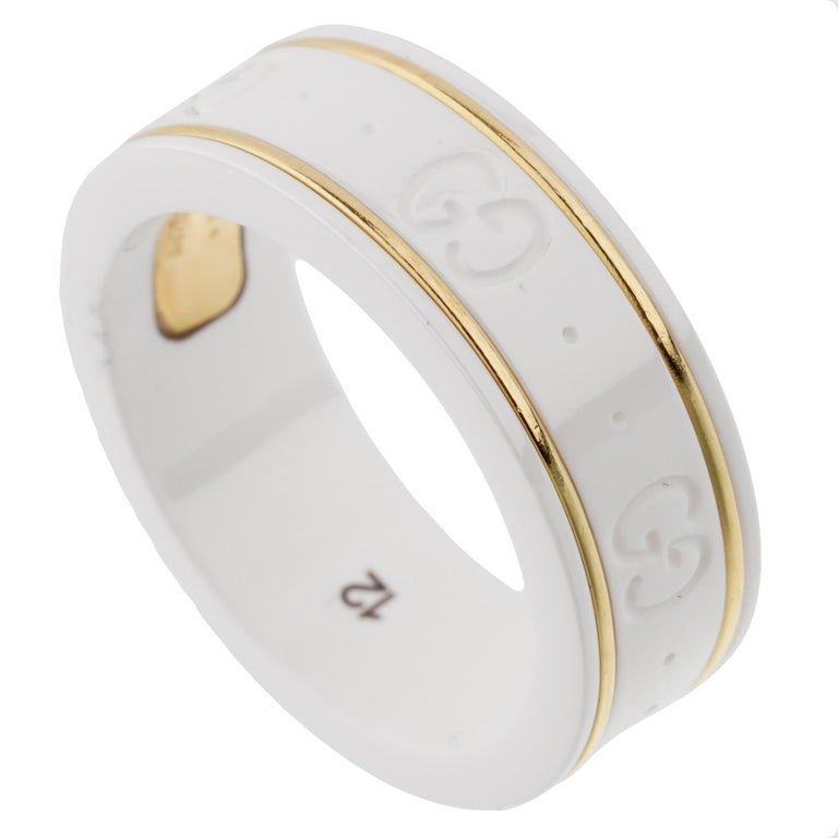A chic GUCCI ceramic ring showcasing the iconic GG motif encircling the band with 2 gold bands. The ring measures a size 6