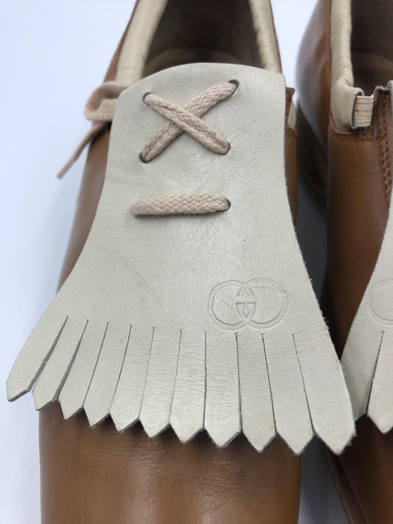 Gucci Collectors Vintage Golf Shoe with marked Gucci Cleats. Tan and Cream with fringe flap. Golf shoe marked inside 39 1/2 ; we tried on the golf shoe and it fits more of a real 8 1/2. This is an ultimate piece for a Gucci collector.  Condition