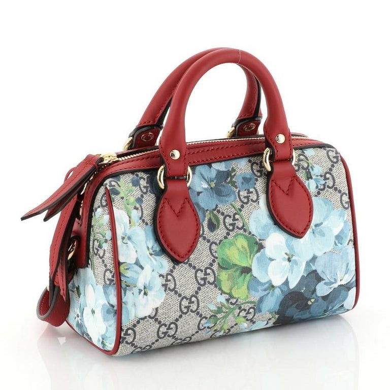 This Gucci Convertible Boston Bag Blooms Print GG Coated Canvas Nano, crafted in blooms print GG coated canvas and red leather, features dual rolled leather handles, leather trim, and gold-tone hardware. Its zip closure opens to a red microfiber