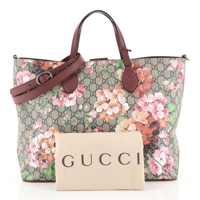 This Gucci Convertible Soft Tote Blooms Print GG Coated Canvas Medium, crafted from brown GG coated canvas with pink blooms print overlay, features dual flat leather handles, leather trim and aged silver-tone hardware. Its magnetic snap closure