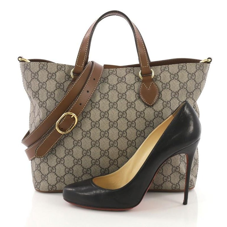 This Gucci Convertible Soft Tote GG Coated Canvas Small, crafted from brown GG supreme coated canvas, features dual rolled handles and gold-tone hardware. Its magnetic snap closure opens to a beige microfiber interior with side zip and slip pockets.