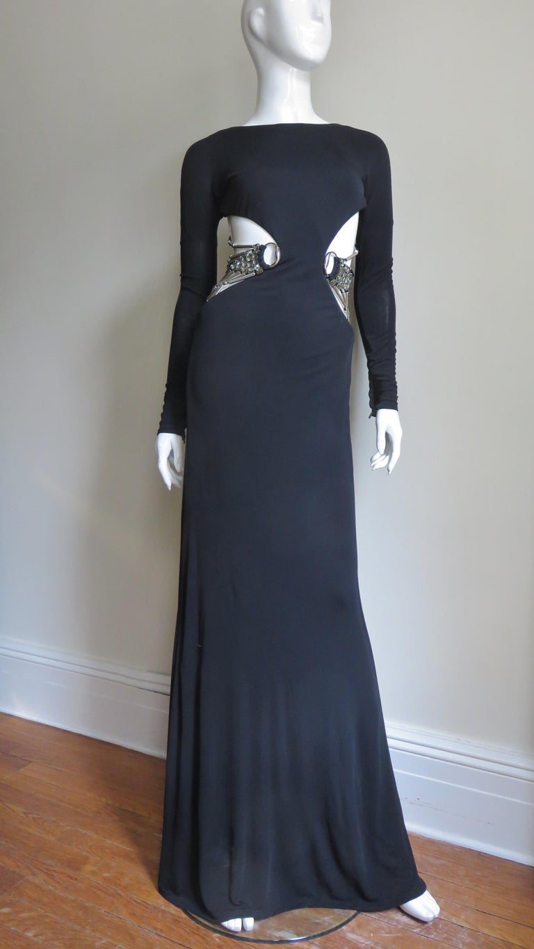 A gorgeous black fine silk knit gown from Gucci.  It is fitted with long sleeves with zipper wrists and fabulous side cut outs from under the bust through to the upper hips.  This cut out is adorned with elaborate Swarovski crystal highlighted metal