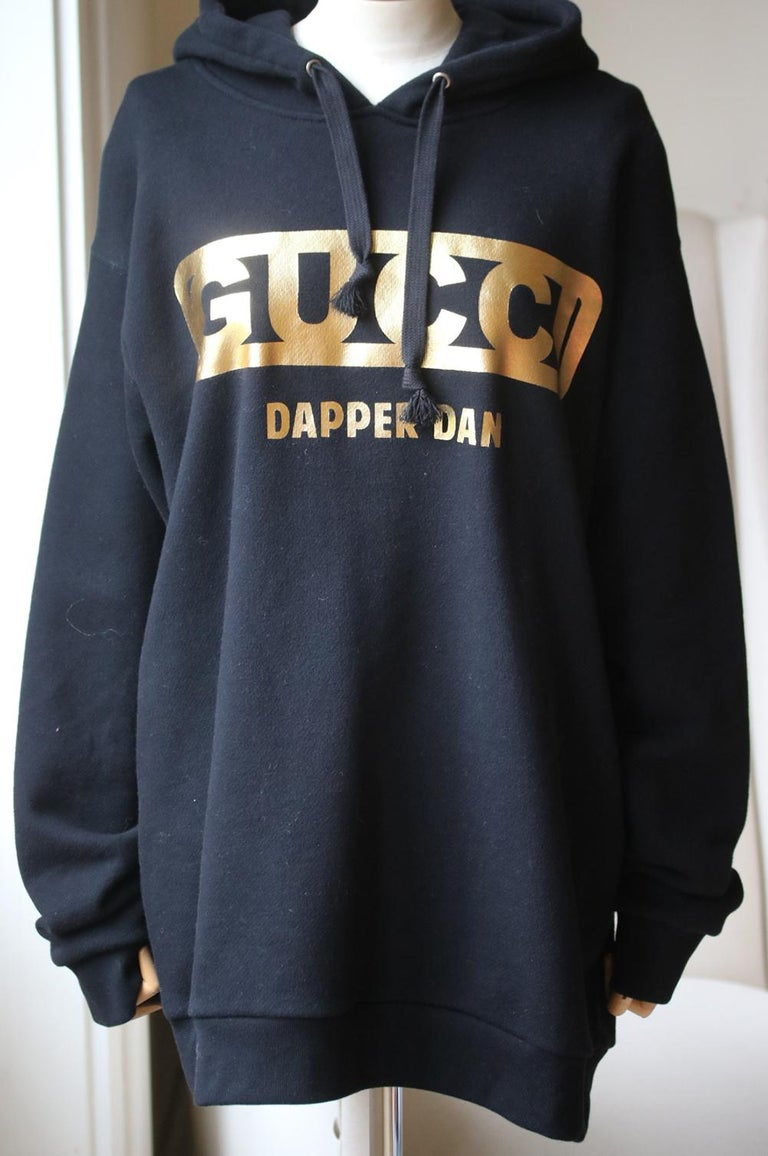 Black felted cotton jersey Laminated gold Gucci-Dapper Dan print. Interior green and red Web Gucci-Dapper Dan label. Fixed hood. 100% cotton. Made in Italy. Colour: black.  Size: Medium (UK 10, US 6, FR 38, IT 42)  Condition: As new condition, no