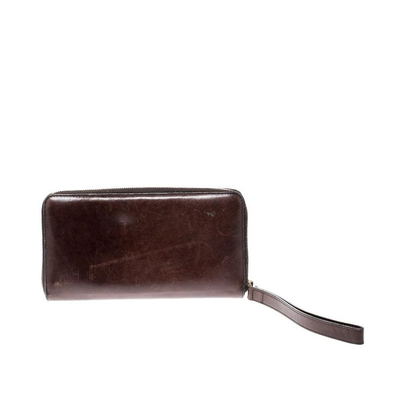 This dark brown wallet from Gucci is worth the buy! It is crafted from leather and features a zip closure that opens to reveal cards slots and a zip pocket. Carry your cash and cards securely in this creation that will fetch you compliments from one