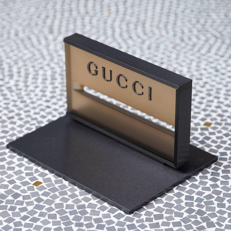 Gucci desk paperweight from the 1980s, this elegant piece is based on an anthrazite metal base and an acrylic stand, attributed to Tom Ford.