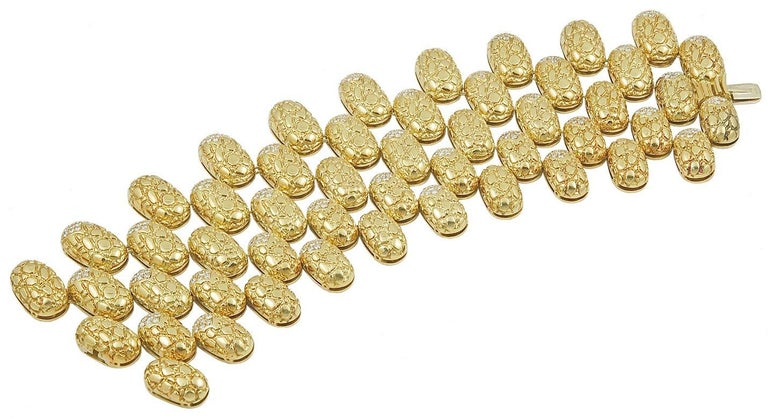Comprising a necklace, magnificently designed as a five-row tiered choker, composed of textured gold oval-shaped bombe links, alternately enhanced by pavé-set diamond accents; a bracelet and pair of ear clips en suite, 14 ins. (necklace), 7 1/4 ins.