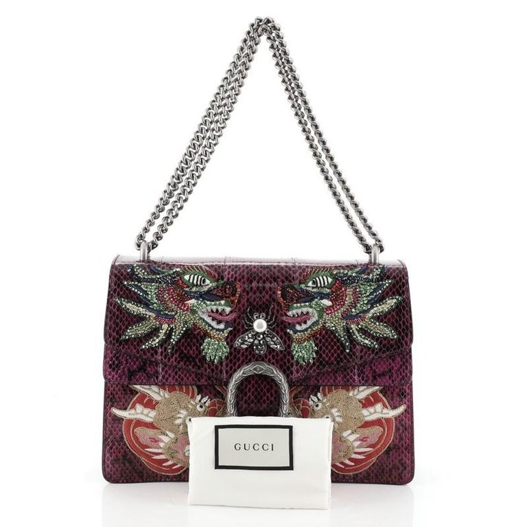 This Gucci Dionysus Bag Embellished Python Medium, crafted from purple genuine python skin with crystal embellishments, features aged silver chain link strap, textured tiger head spur detail on its flap, accordion-like gusseted paneling and aged