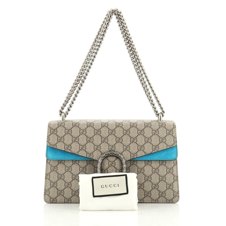 This Gucci Dionysus Bag GG Coated Canvas Small, crafted from brown GG coated canvas, features a sliding chain strap, tiger head spur detail on flap, and aged silver-tone hardware. Its pin closure opens to a blue suede interior with two open