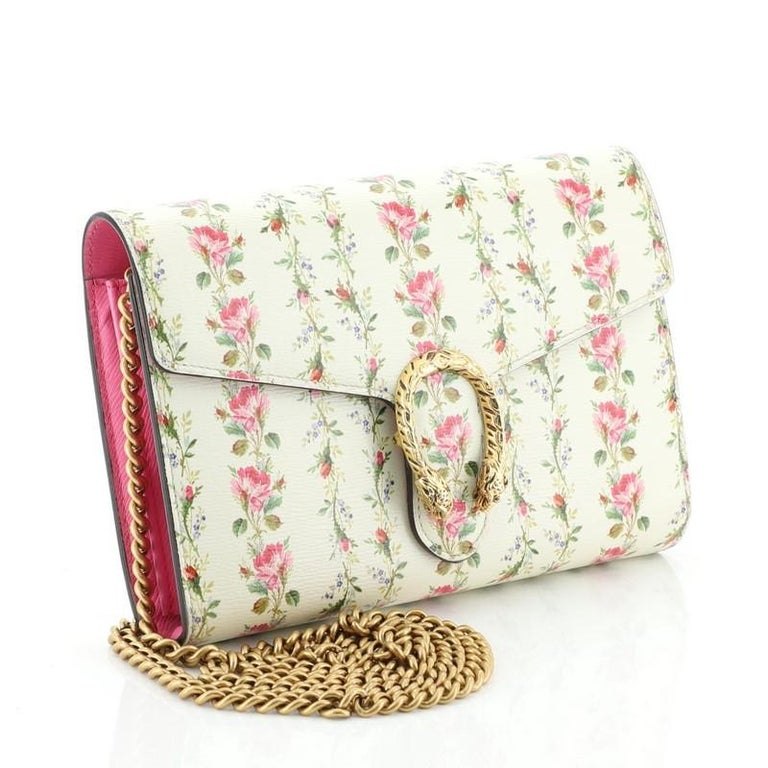 This Gucci Dionysus Chain Wallet Printed Leather Small, crafted from pink neutral and printed leather, features chain link strap, embellished textured tiger head spur detail on its flap, and gold-tone hardware. Its snap button closure opens to a