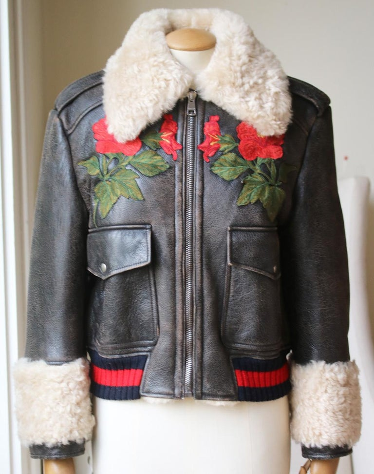 Gucci's shearling lined leather jacket is embroidered with decorative flowers at the chest and a bold LOVED slogan across the shoulders. This cropped Gucci jacket features the label's signature red and blue Web trim finish. Two front flap pockets.
