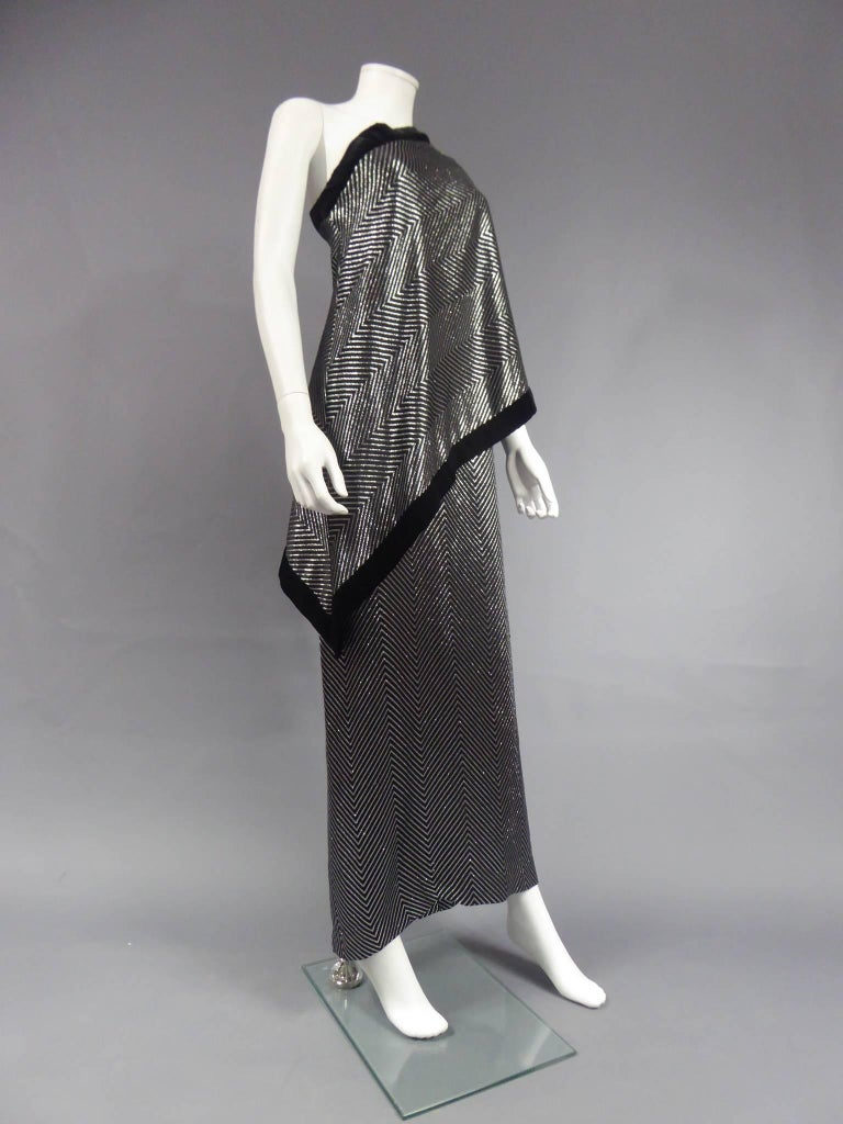 Circa 1980  Italy  Gucci velvet and silver lamé asymmetric tube dress. Wide herringbone patterns of metallic threads. Sleeve on the left side of the cape, cape point on the right side falling on the hips. White label, black graphic, G.GUCCI, made in