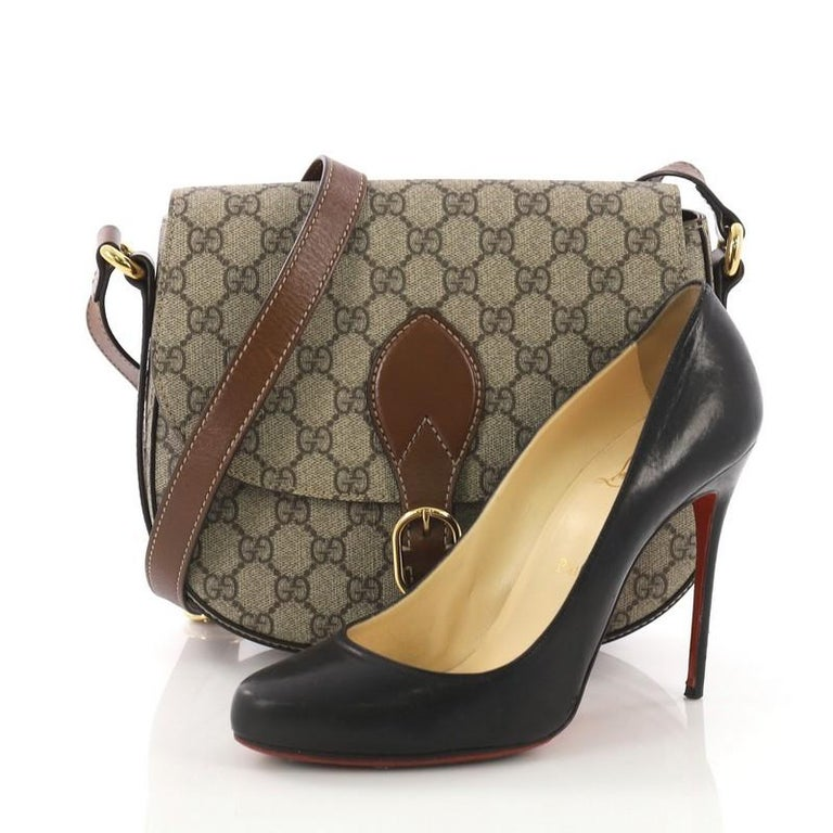This Gucci Flap Saddle Bag GG Coated Canvas Small, crafted in brown GG coated canvas, features an adjustable shoulder strap and gold-tone hardware. It opens to a brown microfiber with zip pocket. **Note: Shoe photographed is used as a sizing