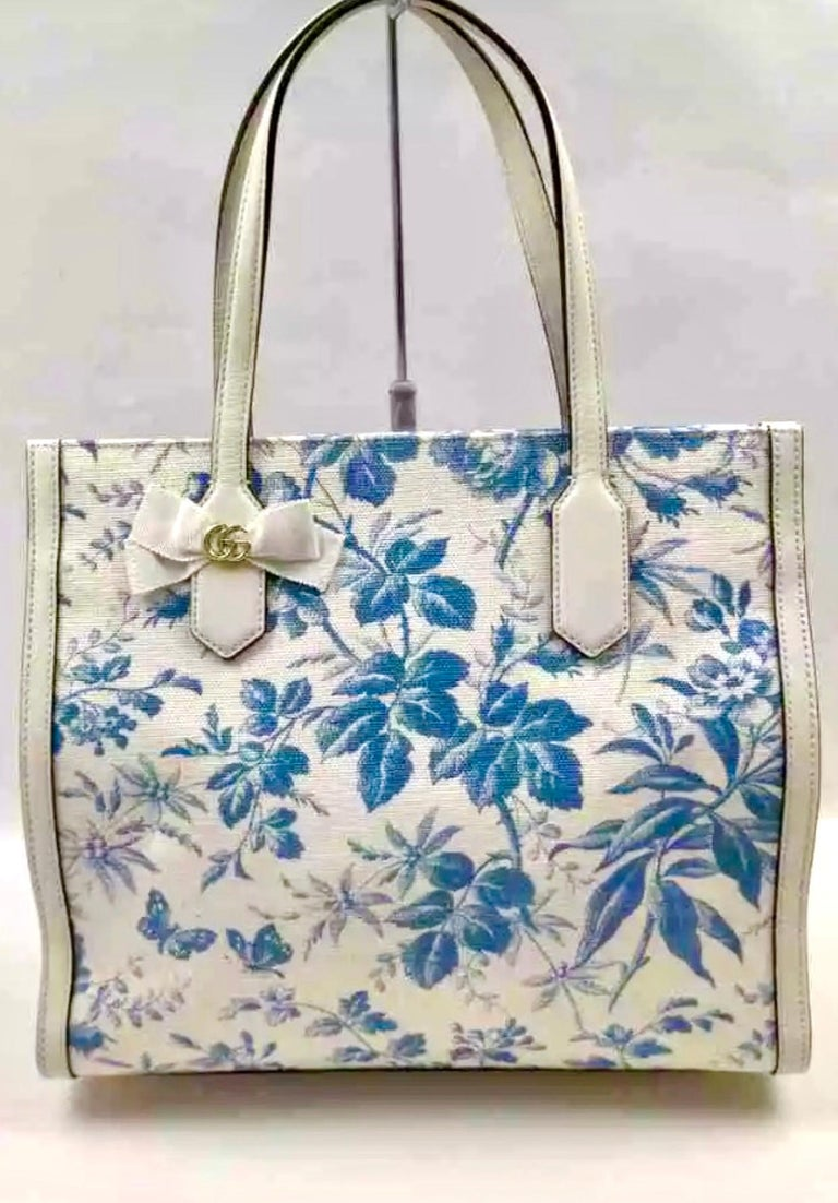 Flora medium leather-trimmed printed canvas tote Latest and Hot   Gucci Flora medium sized handbag. With an off white canvas with a bright colorful floral pattern. The tote features White  leather at the base, trim, and top handles . The top