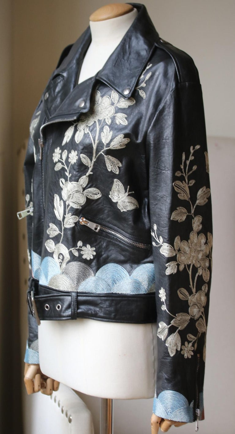 Gucci's leather biker jacket has been hand-embroidered with flowers and butterflies. Framed with metallic silver, dusky-blue and pink thread embroidery. This slim-fit design is lined in silk. Black leather. Asymmetric zip fastening through front.