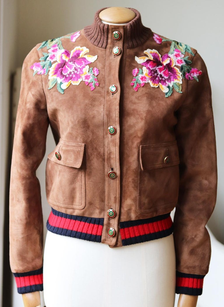 This Gucci jacket is a true example of the label's exceptional craftsmanship with its playfullyembroidered decorative flowers at the chest and a bold LOVED slogan across the shoulders. Made in Italy from brown suede in a boxy silhouette, it's lined