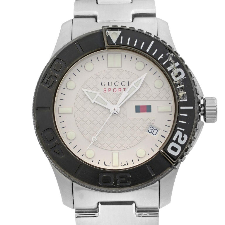 This pre-owned Gucci G-Timeless YA126250 is a beautiful men's timepiece that is powered by quartz (battery) movement which is cased in a stainless steel case. It has a round shape face, date indicator dial and has hand sticks & dots style markers.