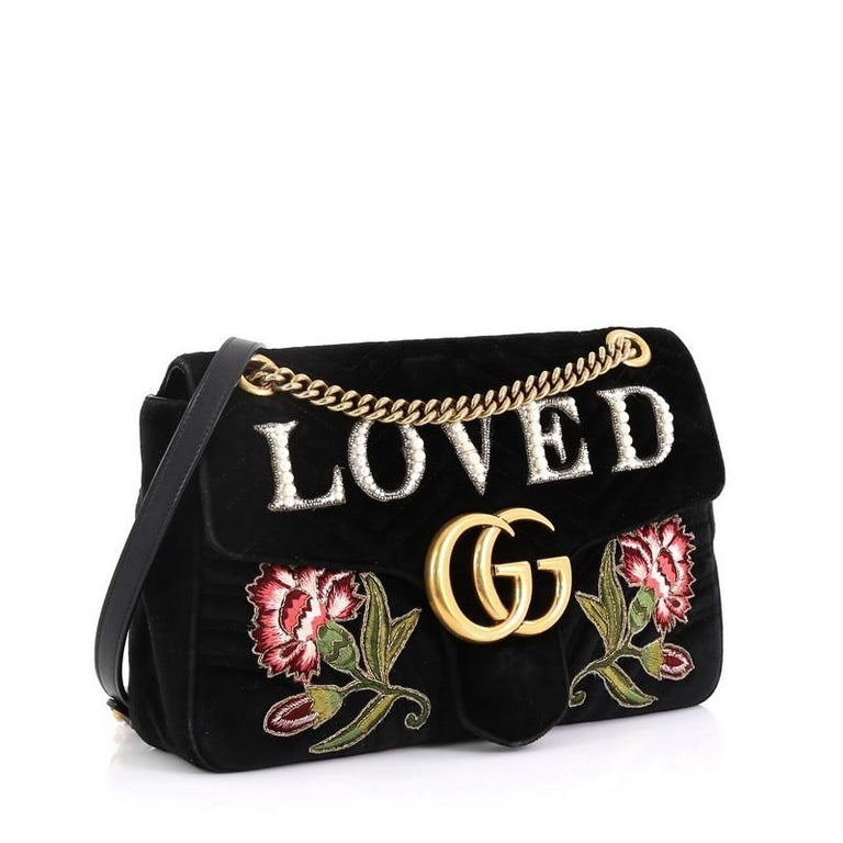 This Gucci GG Marmont Flap Bag Embroidered Matelasse Velvet Medium, crafted in black matelasse velvet, features chain-link shoulder strap with leather pad, embroidered flowers and Swarovski pearls spelling out the word 'Loved', GG logo at front