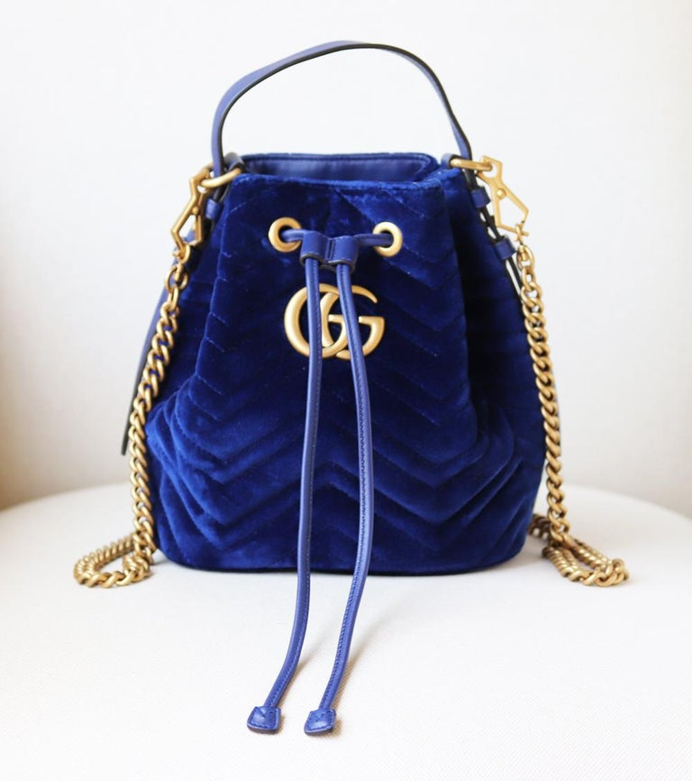 This bucket bag has been made in Italy from plush velvet and decorated with the iconic lettered plaque. The drawstring fastening opens to reveal a pink satin interior inspired by vintage accessories.  Can be carried by its leather handle or