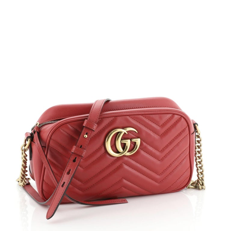 This Gucci GG Marmont Shoulder Bag Matelasse Leather Small, crafted from red matelasse leather, features a leather strap with chain links, GG logo at the front, and aged gold-tone hardware. Its zip closure opens to a neutral microfiber interior with