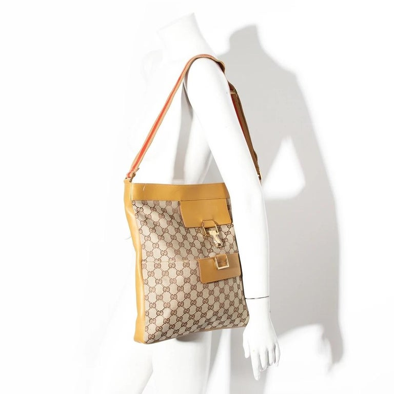 Gucci by Tom Ford Messenger Bag  Made in Italy  Classic tan canvas with iconic interlocked GG pattern  Light brown leather detailing Gold hardware closure  Gold hardware clasp has Gucci labeled plastic covering  Open pocket along front of bag Webbed