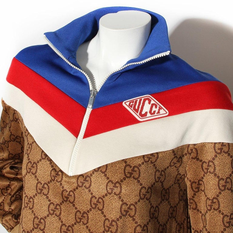 Gucci by Alessandro Michele  Circa Pre-Fall 2018 Made in Italy  Brown monogram print Red, white and blue stripe around collar/bust Rubber logo patch at left chest Quarter zip Dual front zip pockets Back pleat  Technical jersey, polyester blend