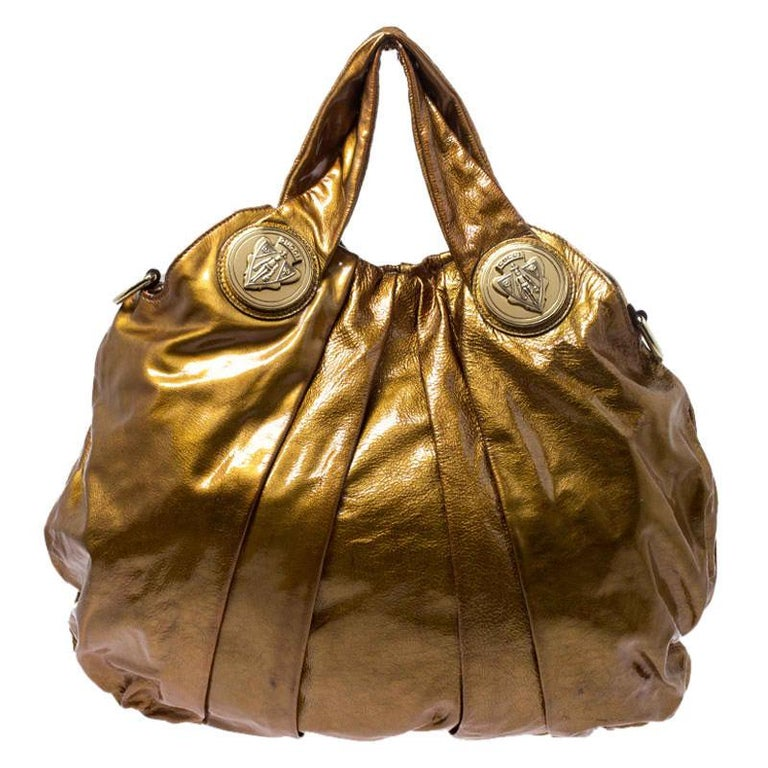 This Gucci hobo is built for everyday use. Crafted from patent leather, it is accented with Gucci's iconic gold-tone crest. The nylon insides are sized well for housing your essentials comfortably. Designed with two top handles and a detachable