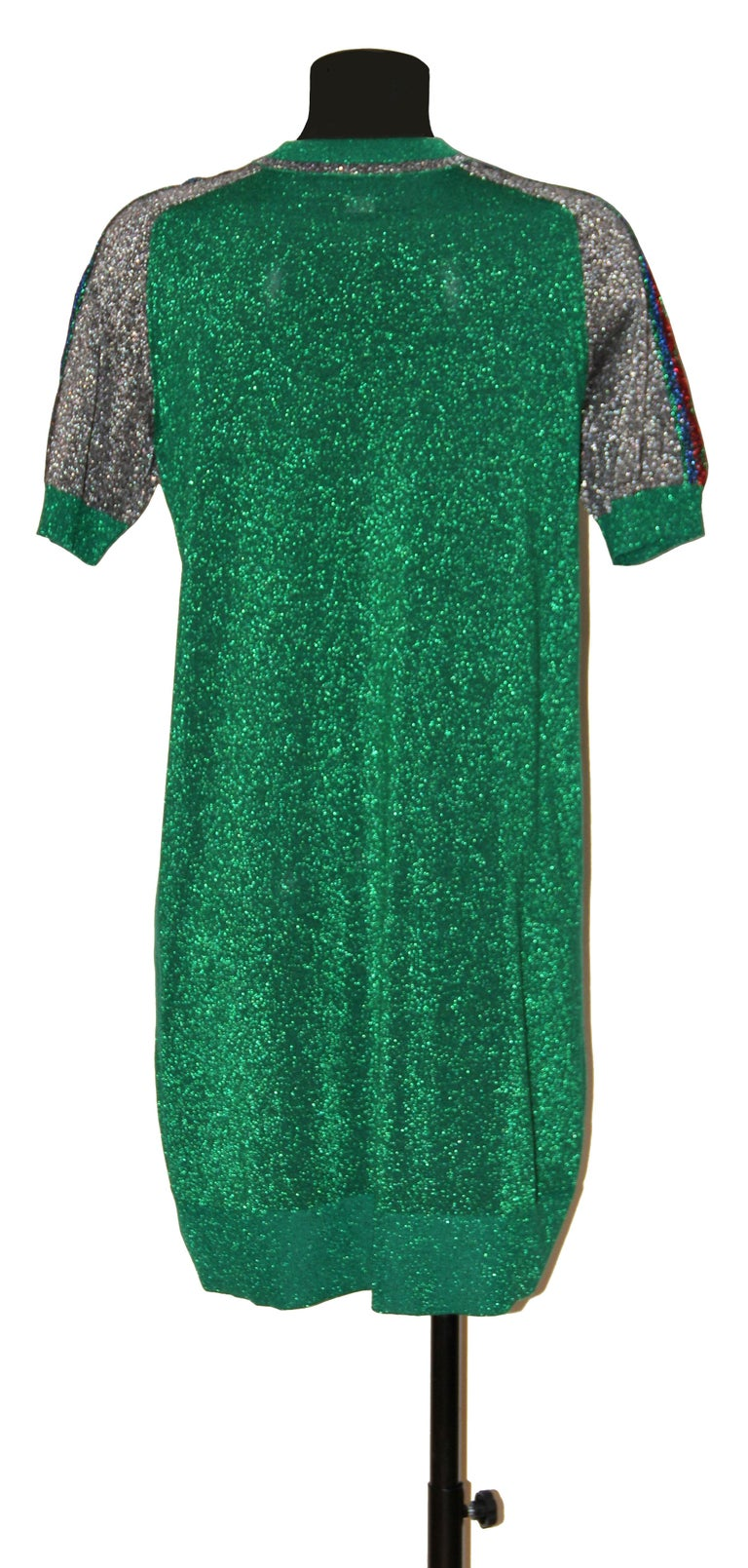 This pre-owned but new green metallic dress has a sporty chic look ! It features the red and green Gucci Ruabn stripe and logo motifs down the shoulders.  It has a round neck, short sleeves and is cut for a knee-length T-shirt silhouette.  Fabric: