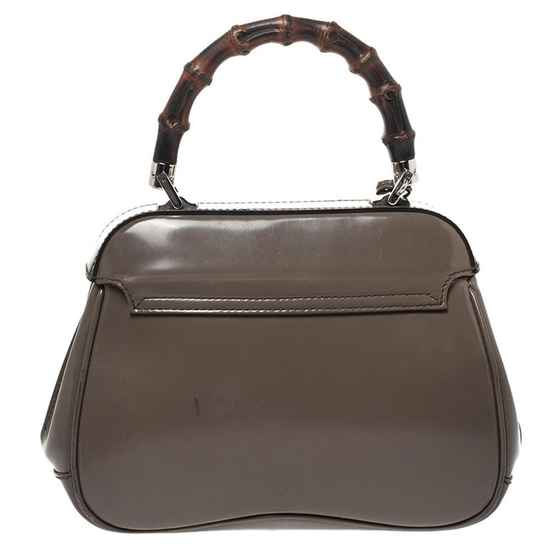 Featuring the iconic Lady Lock, this top handle bag is from Gucci. This bag is crafted from grey-hued leather and features a signature bamboo top handle. The push-lock closure opens to a suede-lined interior that houses an open compartment. Carry