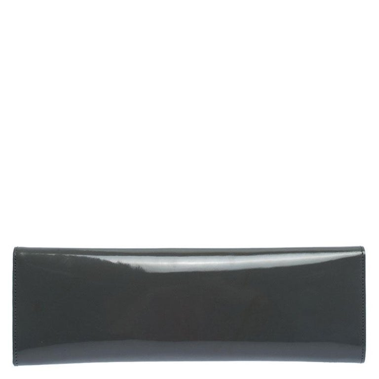 This sleek Sigrid clutch from the house of Gucci is a masterpiece. Crafted in Itlay, it is made of glossy patent leather and comes in a stunning shade of grey. It features a front flap which features delicate silver-tone cutout detailing and the
