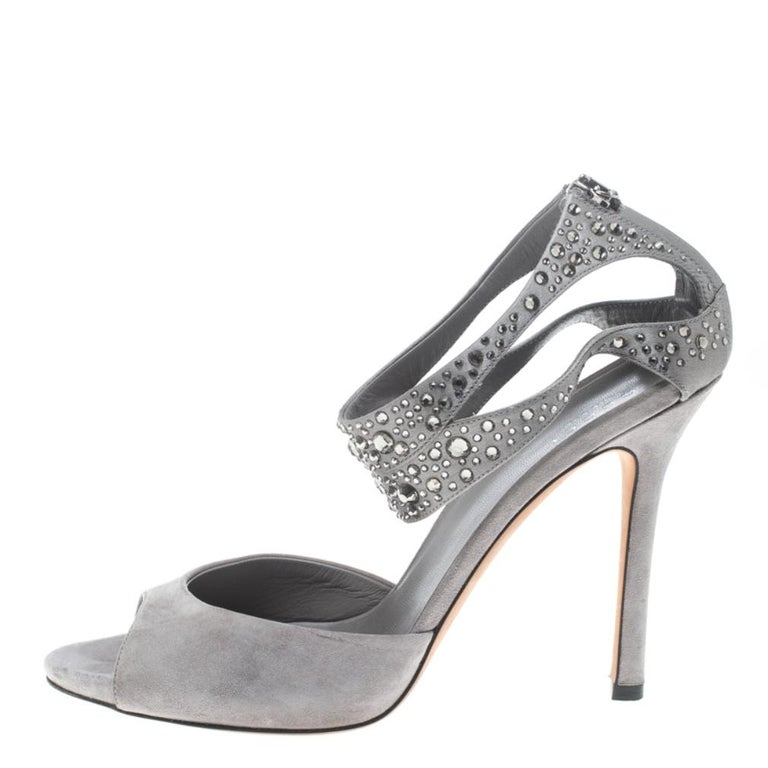 Gucci never fails to impress and yet again charms us with these splendid sandals. The grey sandals are crafted from suede and satin and feature an open toe silhouette. They flaunt single vamp straps and crystal embellished cutout ankle straps.