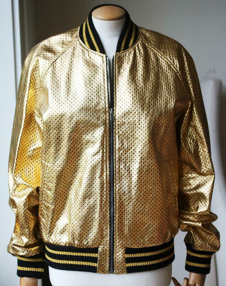Gold leather with black stars and Guccy in SEGA font. Knit trim. Front pockets. Zip closure. Cotton lining. Made in Italy. Colour: gold. 100% Lambskin leather.  Size: IT 44 (UK 12, US 8, FR 40)  Condition: As new condition, no sign of wear.
