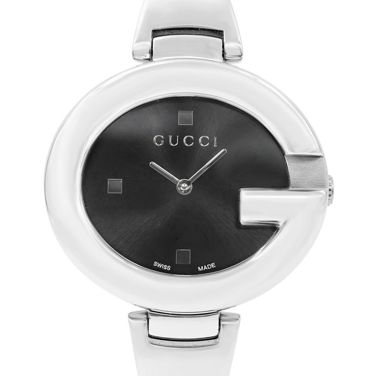 This pre-owned Gucci Guccissima  YA134301 is a beautiful Ladie's timepiece that is powered by quartz (battery) movement which is cased in a stainless steel case. It has a oval shape face, no features dial and has hand dots style markers. It is
