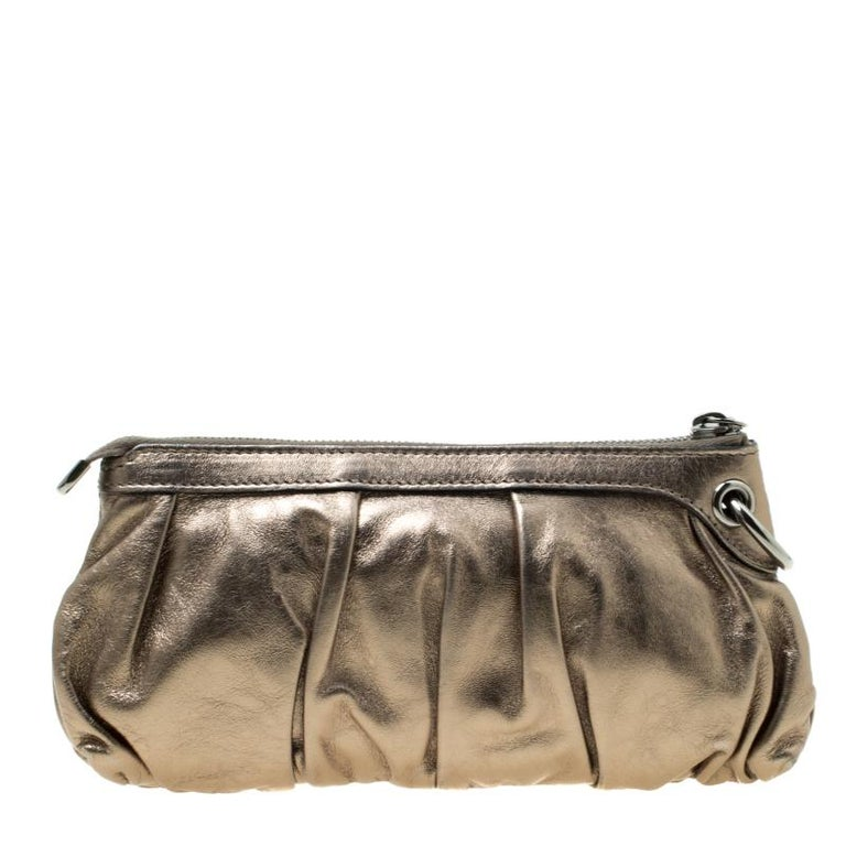 Have all eyes on you when you flaunt this stunner of a clutch by Gucci. Crafted from leather, it carries a metallic shade and a zipper which secures the leather interior for your essentials. Tassels with bamboo touches make the clutch