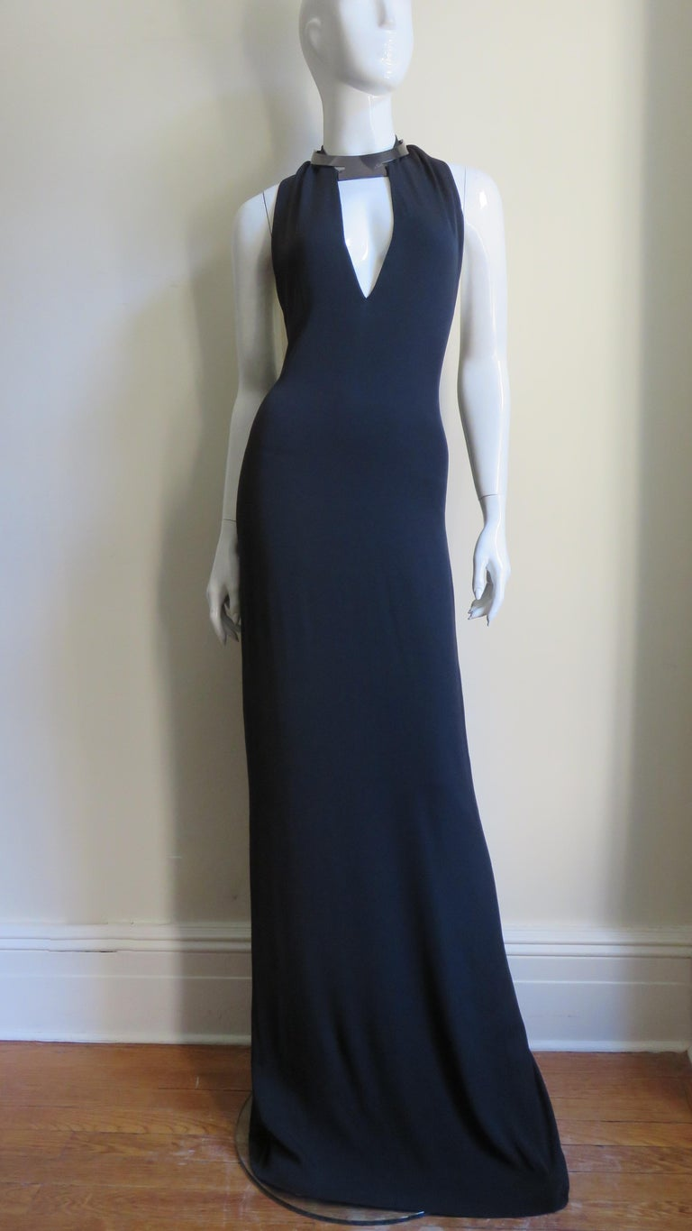 A gorgeous elegant black silk dress from Gucci S/S 2010 collection. The halter style dress has a front plunging cut out below a fabulous silver grey choker style collar with adjustable leather straps that close at the back of the neck. The dress