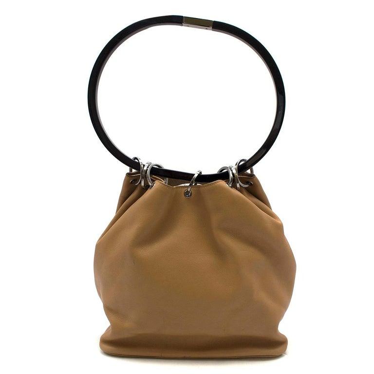Gucci hoop-handle leather bucket bag   - Tan-brown, soft leather  - Black oversized resin ring handle - Gunmetal hardware  - Logo-debossed back - Open top  - Internal zip pocket  - Tan-brown suede lining  - Branded dust bag included   Please note,