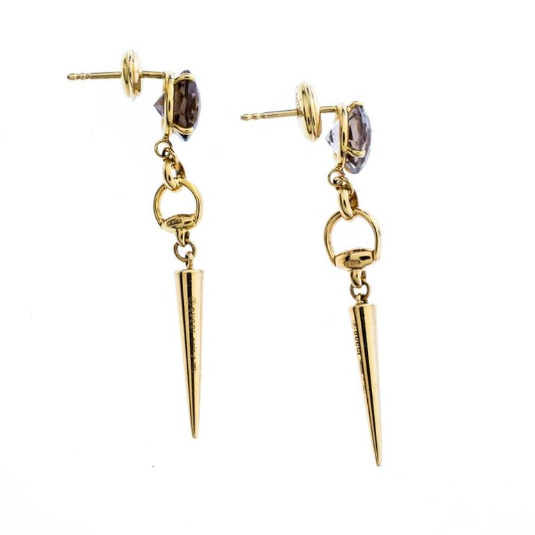 Perfectly designed for a statement look, these drop earrings from Gucci flaunt the iconic Horsebit motif in a refreshing style. The pair features smoky quartz stone studs with 18k yellow gold horsebit-like spike drops. These beauties are not only