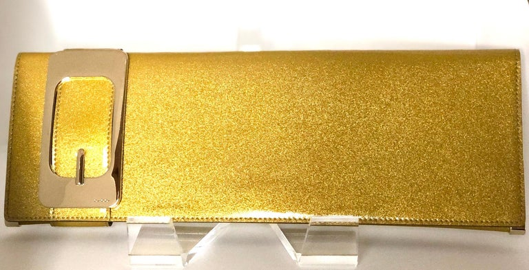 Offered is a Gucci iridescent gold patent leather elongated clutch handbag with gold metal accents and tan suede interior.  Make:  Gucci (label states Gucci Made in Italy Place of Manufacture:  Italy Material used:  Patent leather and gold tone