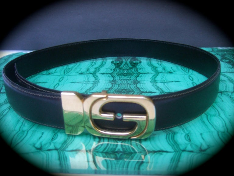 Gucci Italy black & brown reversible leather unisex belt c 1980 The stylish belt is adorned with a sleek gilt metal buckle with Gucci's iconic interlocked G.G. initials  Designed with a rotating buckle that allows for the belt to be worn on either