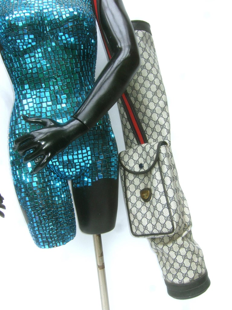 Gucci Italy Extremely rare blue monogram golf bag c 1980s The compact size golf bag is covered with Gucci's iconic coated blue coated canvas with their signature inverted G.G. monogram  Carried with a red & blue canvas webbed striped handle